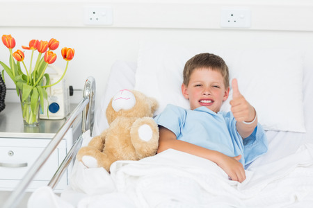 Portrait of little boy gesturing thumbs up with teddy bear in hospital bed photo