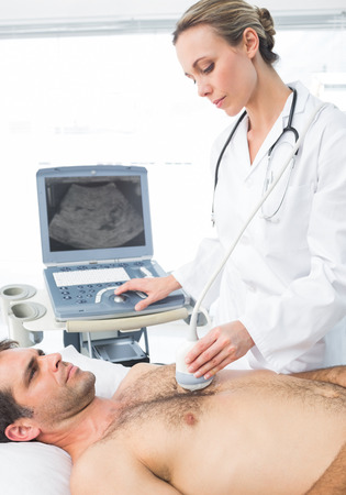 Female cardiologist giving a heart ultrasound to male patient photo