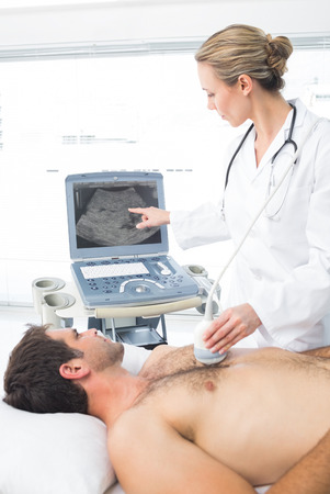 sonogram: Female doctor using sonogram on male patient in examination room