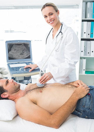 Confident female doctor using sonogram on male patient in examination room photo