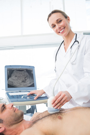 Confident female doctor using ultrasound scan on male patient in examination room photo
