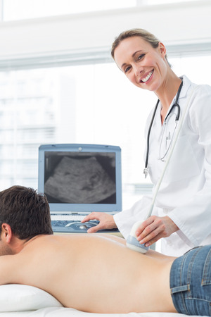Happy female doctor performing ultrasound scan on back of male patient photo
