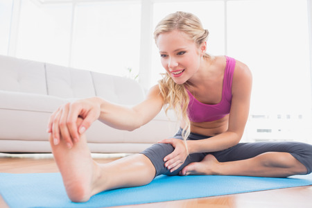 touching toes: Toned blonde stretching on exercise mat at home in the living room