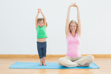 Pregnant mother and daughter doing yoga together in a fitness studio photo