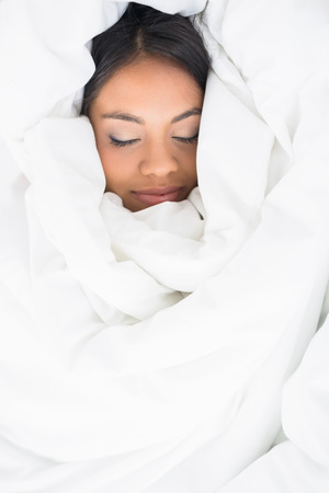 wrapped up: Sleeping girl wrapped up in her duvet in her bedroom at home
