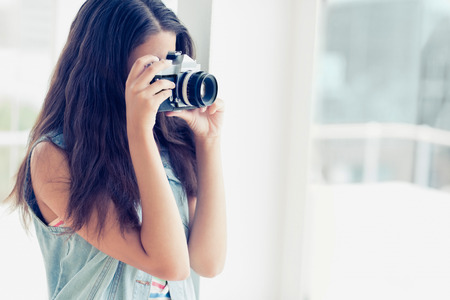 Stylish young photographer taking a photo in a bright room photo