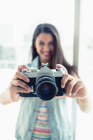 Happy young woman taking a photo at camera in a bright room photo