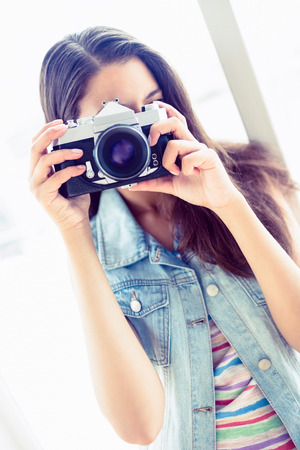 Smiling young woman taking a photo in a bright room photo