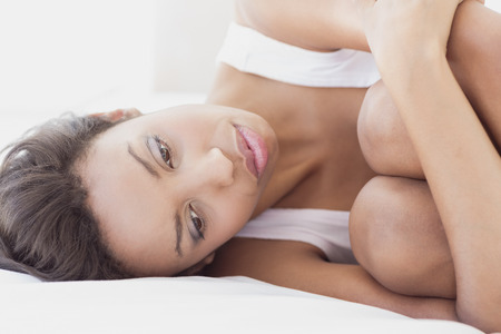 pessimistic: Unhappy brunette lying on bed hugging her knees at home in the bedroom Stock Photo