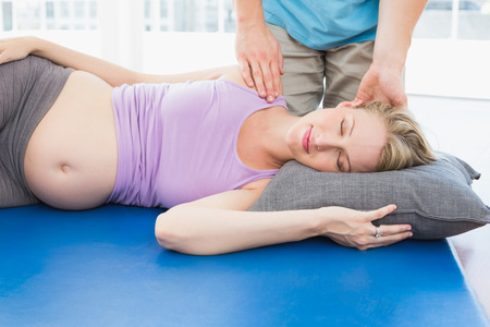 Blonde pregnant woman having a relaxing massage in a studio photo