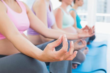 Vreedzame zwangere vrouwen mediteren in yoga les in een fitness studio