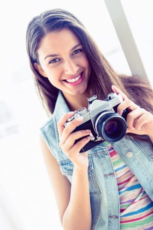 Smiling young woman holding her camera in a bright room photo