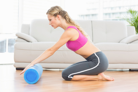 Fit blonde kneeling on floor using foam roller at home in the living room photo