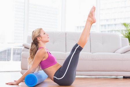 Fit blonde stretching on floor using foam roller at home in the living room photo