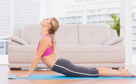 Fit blonde doing yoga on exercise mat at home in the living room photo