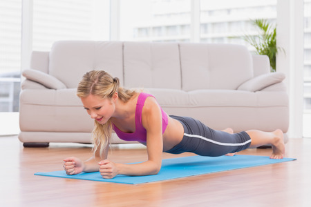 plank position: Fit blonde in plank position on exercise mat at home in the living room Stock Photo