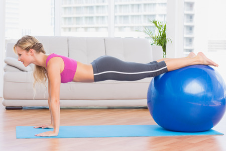 plank position: Slim blonde in plank position using exercise ball at home in the living room Stock Photo