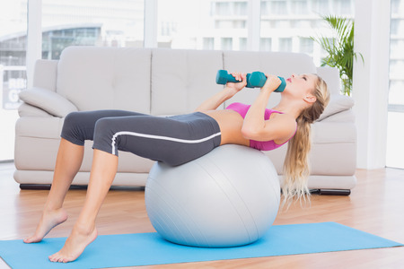 Smiling blonde doing sit ups with exercise ball holding dumbbells at home in the living room photo
