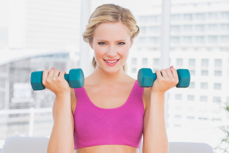Cute blonde lifting dumbbells and smiling at home in the living room photo