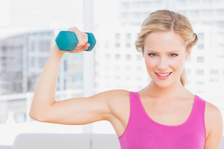 Happy blonde lifting dumbbell and flexing at home in the living room photo