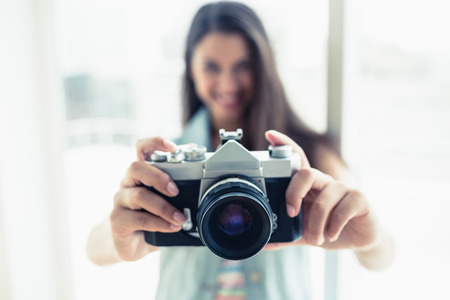 Stylish young woman taking a photo at camera in a bright room photo