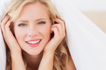 Cheerful blonde smiling at camera from under the duvet at home in the bedroom Stock Photo