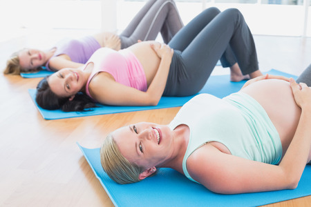 fit women: Happy pregnant women in yoga class lying on mats in a fitness studio