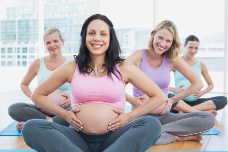 mujeres embarazadas: Mujeres embarazadas felices en la clase de yoga sosteniendo sus golpes en un gimnasio
