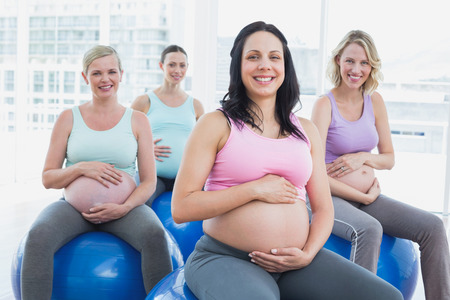 Smiling pregnant women sitting on exercise balls  in a fitness studio photo