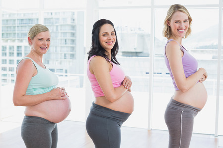 Pregnant women standing in a line smiling at camera in a fitness studio photo