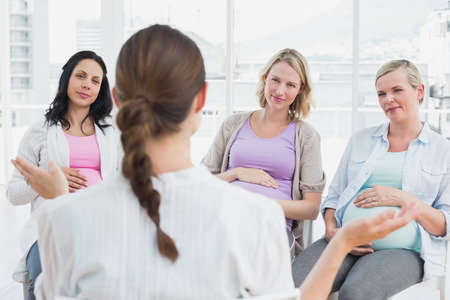 Pregnant women listening to gesturing doctor at antenatal class at the hospital