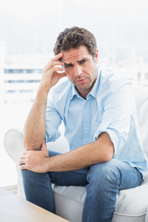 Man with headache sitting on the couch looking at camera at home in the living room Stock Photo