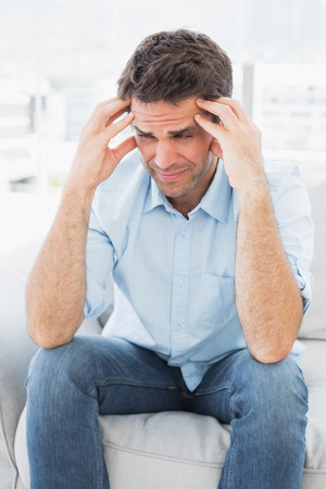 Grimacing man sitting on the couch with a headache at home in the living room Stock Photo