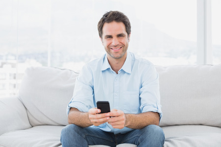 Cheerful man sitting on the couch sending a text message at\ home in the living room