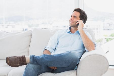 電話をかける自宅リビング ルームでソファに座っての陽気な人