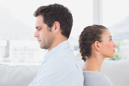 Unhappy couple sitting back to back on the couch at home in the living room