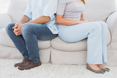 Couple sitting back to back on the couch at home in the living room photo