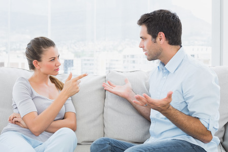 accusing: Couple having a serious argument on the couch at home in the living room Stock Photo
