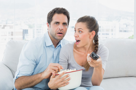 Couple watching scary movie on the couch with bowl of popcorn at home in the living room photo
