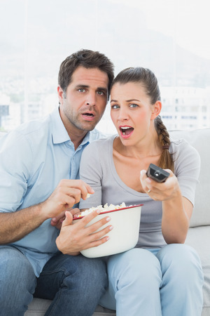Couple watching scary movie on the sofa with bowl of popcorn at home in the living room photo