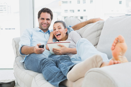 Couple watching funny movie lying on the sofa with bowl of popcorn at home in the living room photo