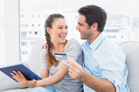 Laughing couple sitting on the couch shopping online with tablet pc at home in the living room photo