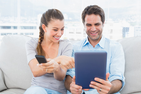 Happy couple sitting on the couch using tablet pc and watching tv at home in the living room photo