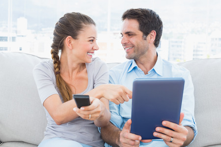 Smiling couple sitting on the couch using tablet pc and watching tv at home in the living room photo