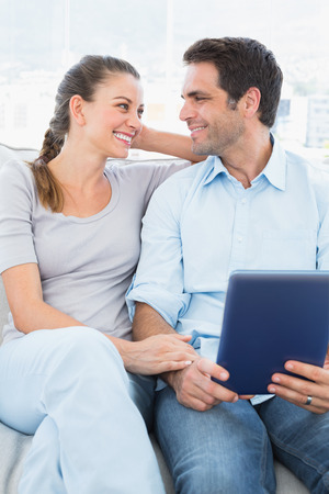 Cute couple sitting on the couch using tablet pc at home in the living room photo
