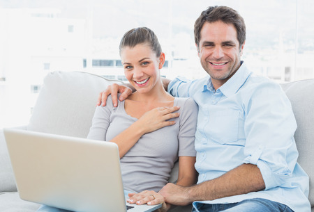 Happy couple sitting on the couch using laptop together at home in the living room photo
