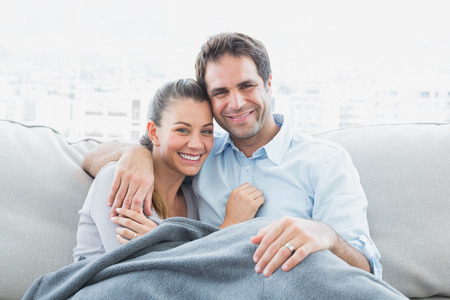 Cheerful couple relaxing on their sofa smiling at camera under blanket at home in the living room photo