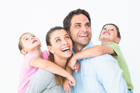 looking up: Happy young family looking up together on white background Stock Photo