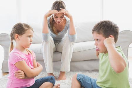 Beu moeder te luisteren naar haar jonge kinderen vechten thuis in de woonkamer