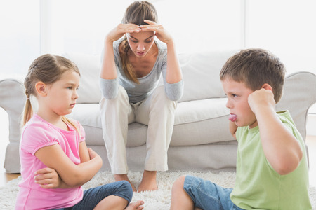 mother child: Fed up mother listening to her young children fight at home in the living room Stock Photo